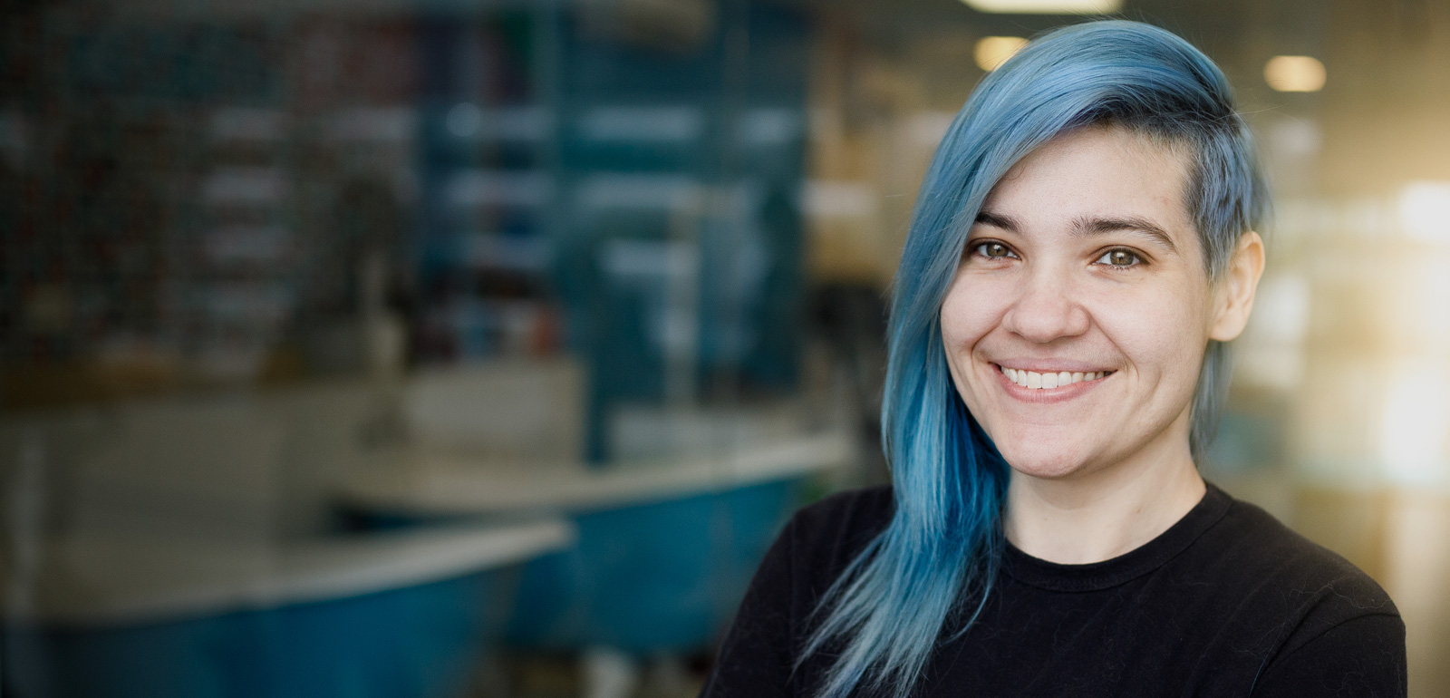 Woman with blue hair smiles