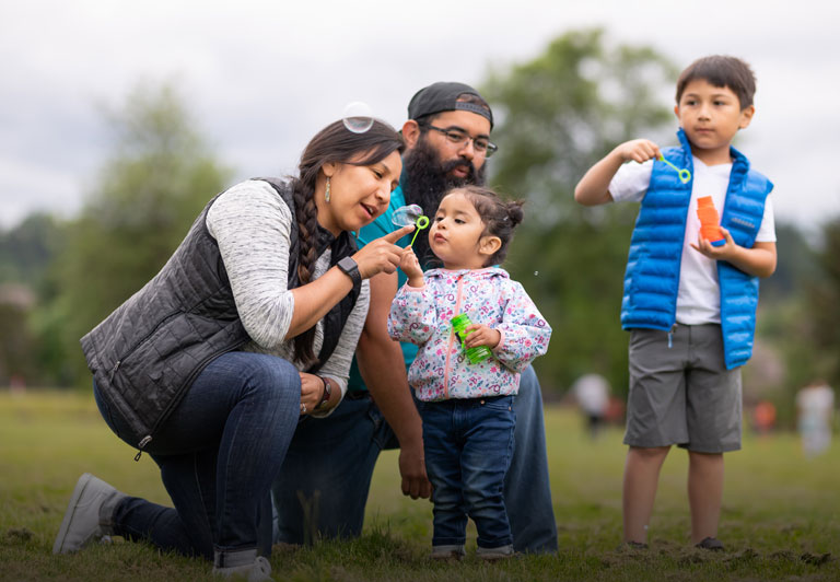 Native American community: a family enjoys the day outdoors, blowing bubbles.