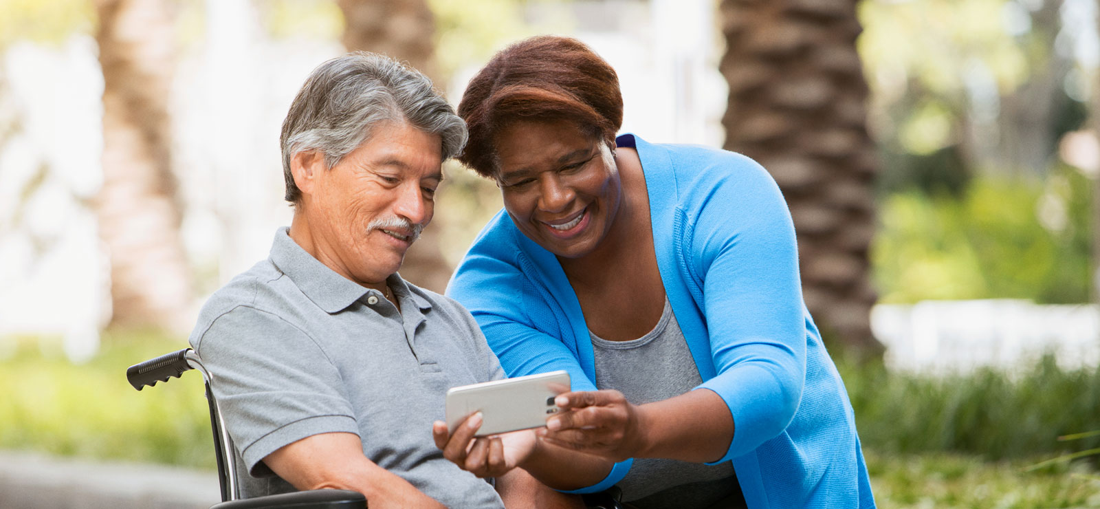 Smiling woman leans in to show man in wheel chair a smart phone screen.