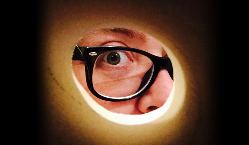 Person with glasses looking through a cardboard tube