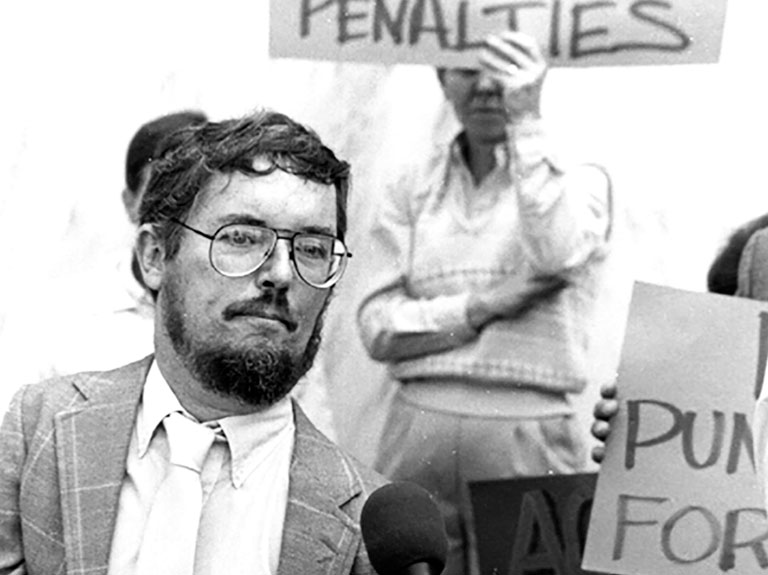 Historian Paul Longmore - Man dressed in suit and wearing glasses stands behind microphone at rally with people holding signs in the background