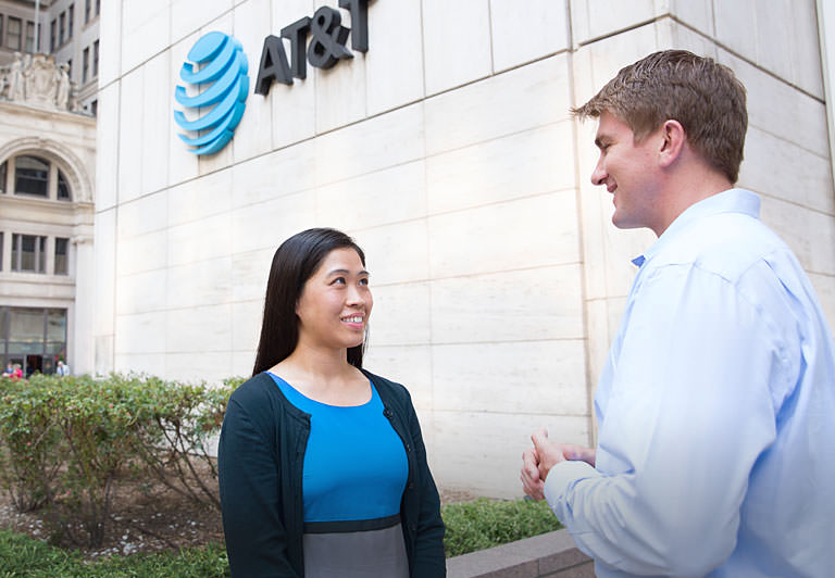 Two AT&T employees talking outside of an AT&T building
