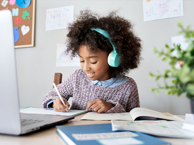 A schoolgirl smiles while writing with her Apple Pencil and listening to headphones