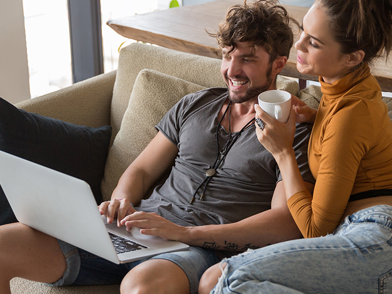 Man and women sit on a couch together and look at a laptop