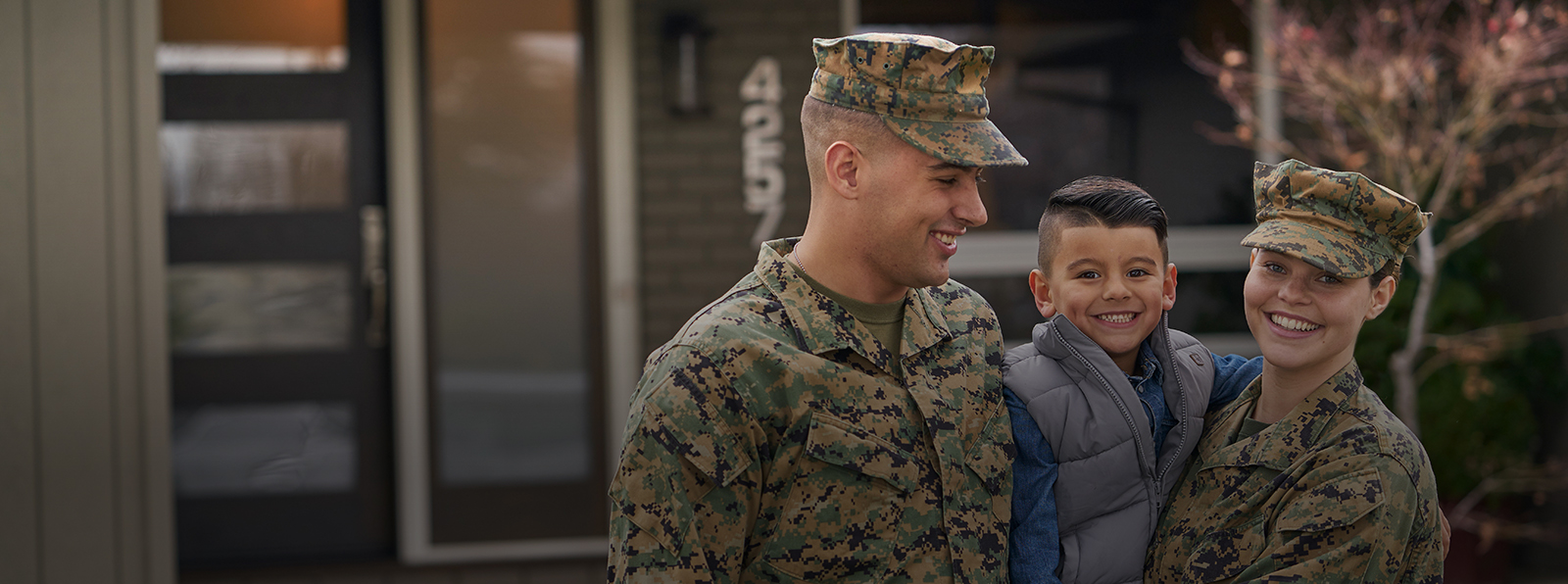 Image of Military Family with child in front of house.